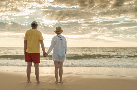 mid fifties: Senior man and woman holding hands of each other at the beach Stock Photo