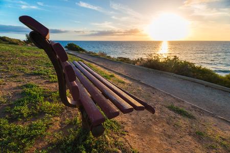 ocea: Bench on sea coast at sunset
