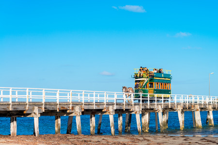 brige: Victor Harbor, South Australia - April 4, 2015: People are riding the horse-drawn carriage from the Granite Island back to the main land. Victor Harbor is one of the most popular tourist attractions in South Australia.