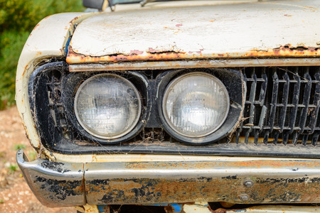 rusty car: Old abandoned rusty car covered with web. Front view