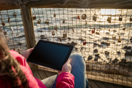 business security: Woman using tablet at the beach during sunset