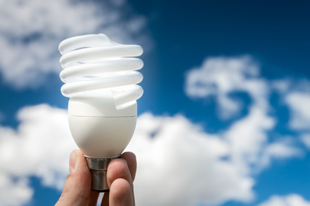 Energy efficient bulb in hand with blue sky in background Stock Photo