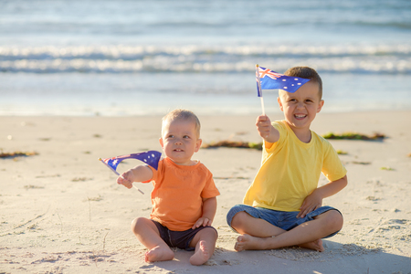 Smiling kids with flags of Australia at the beach 写真素材