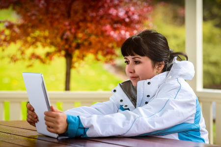 gprs: Woman sitting inside gazebo and holding tablet in autumn park Stock Photo