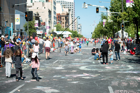 credit union: Adelaide, South Australia - November 14, 2015: Kids drawing with chalk on the street during Credit Union Christmas Pageant 2015. Christmas Pageant is a community event with fantasy and fairy floats, colourful characters, clowns, bands, dancers and more! Editorial