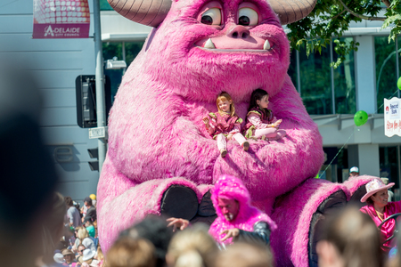 credit union: Adelaide, South Australia - November 14, 2015: Two girls riding the Big Friendly Bruto character. Christmas Pageant is a community event with fantasy and fairy floats, colourful characters, clowns, bands, dancers and more!