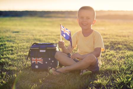 australia day: Custe smiling kid with flag of Australia sitting on the grass at sunset on Australia Day Stock Photo