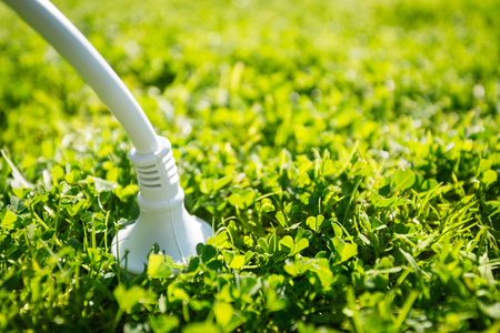 saving electricity: Power plug coonnected to the green source of energy Stock Photo