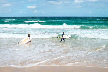 going places: Sydney, Australia - November 8, 2015: Little girl and boy going for surfing at Bondi Beach on a day. Bondi beach is one of the most famous places for surfing in Australia