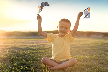 australia day: Happy boy with flags of Australia sitting on the grass at sunset on Australia Day