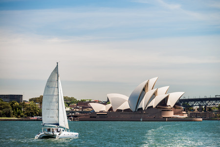 performing arts: Sydney, Australia - November 10, 2015: Boat passing by the Sydney Opera House. Opera House is a multi-venue performing arts centre identified as one of the 20th centurys most distinctive buildings.