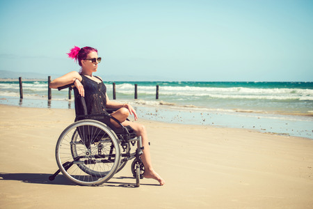 disadvantaged: Disabled woman in the wheelchair at the beach. Cross-processed and color-toned image. Stock Photo