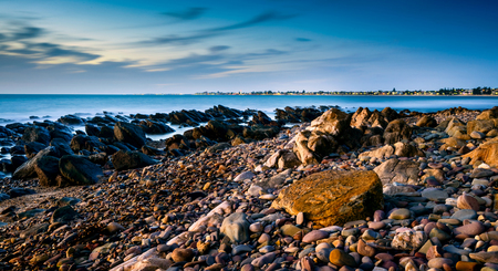 applied: Dramatic sunset on the rocky beach, South Australia. Long exposure settings applied. Stock Photo