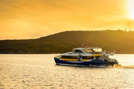 manly: Sydney, Australia - November 10, 2015: Manly Fast Ferry boat heading to Sydney Cirqular Quay with passengers onboard on a warm sunny evening.