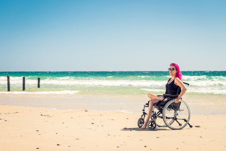 disadvantaged: Disabled woman in the wheelchair at the beach. Cross-processed and color-toned image Stock Photo