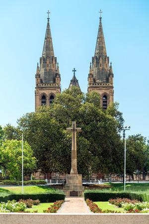 sacrificio: Cross of Sacrifice with St Peters Cathedral on the background, Pennington Gardens, South Australia Foto de archivo
