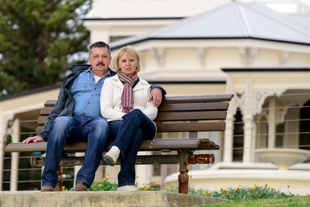 late fifties: Senior couple in their late fifties sitting on the bench in Australian countryside