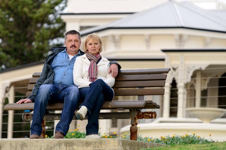 Senior paar in hun late jaren vijftig, zittend op de bank in de Australische platteland