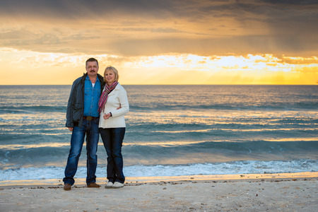 mid fifties: Senior couple standing at the beach and showing positive emotion