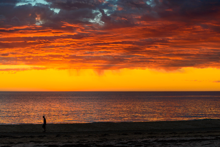 unrecognisable people: Unrecognisable man walking along the beach during dramatic sunset and storm clouds