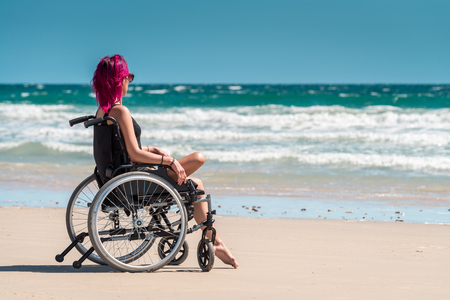 disadvantaged: Disabled woman in the wheelchair at the beach enjoying the view Stock Photo