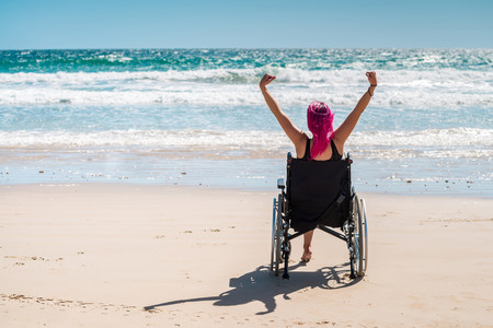 disadvantaged: Disabled woman in the wheelchair at the beach Stock Photo