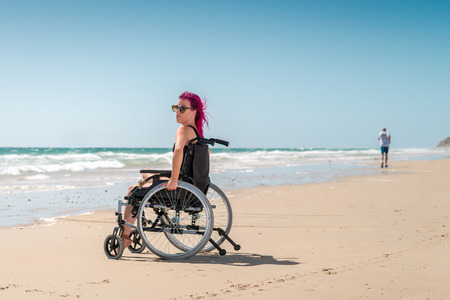 disadvantaged: Disabled woman enjoys the beach and sun while the man was running by