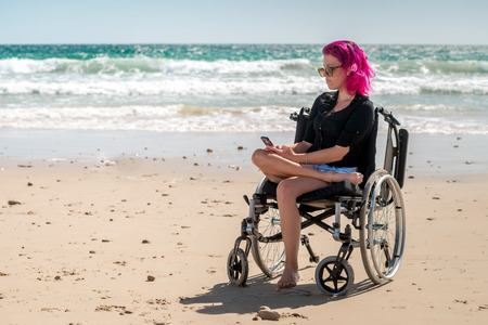 disadvantaged: Disabled woman using mobile phone at the beach on a bright day Stock Photo