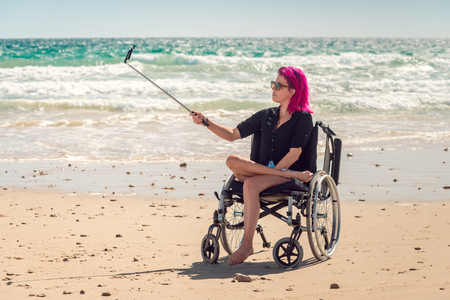 disadvantaged: Disabled woman in the wheelchair at the beach taking selfie photos with her mobile phone on selfie stick