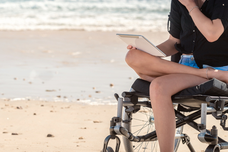 disadvantaged: Young woman in wheelchair using  tablet at the beach