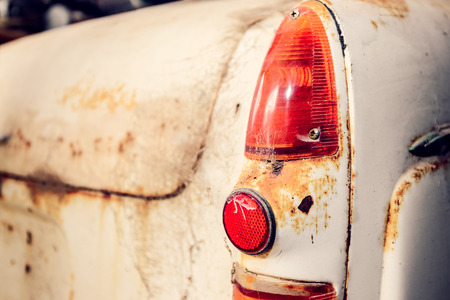 tail light: Rear view of old abandoned car with cracked tail light covered with web. Color-toning effect applied.