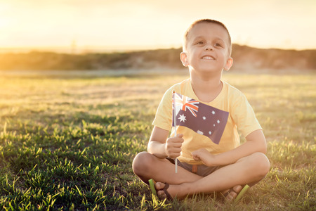 Boy with Australian Flag sitting on the grass on Australia Day at sunset