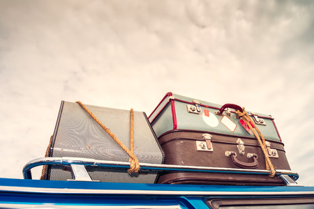 Pile of vintage bags on roof of the car fastened with rope. Color-toning applied Stock Photo
