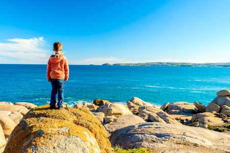 elliot: Boy standing at the edge of the rock and looking into the sea at Port Elliot, South Australia