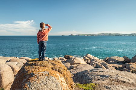 elliot: Boy standing at the edge of the rock and looking into the sea at Port Elliot, South Australia. Color toning applied