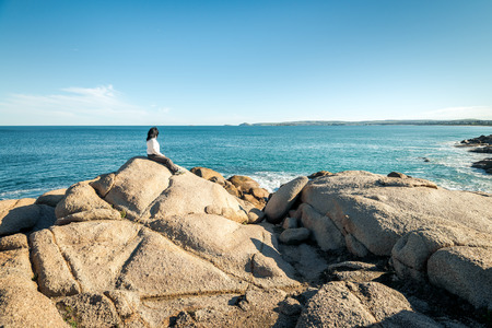 elliot: Woman sitting at the edge of the rock and looking into the sea at Port Elliot, South Australia Stock Photo