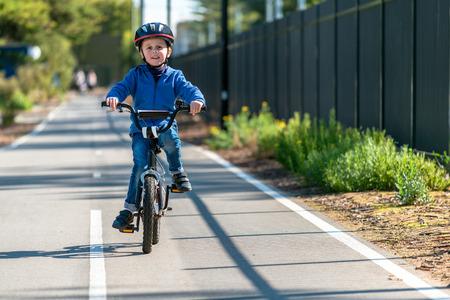 Happy aussie boy riding his bicycle on bike lane on a day, South Australia