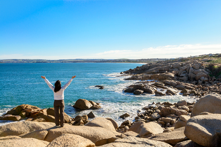 elliot: Woman standing at the edge of the rock and looking into the sea at Port Elliot, South Australia Stock Photo