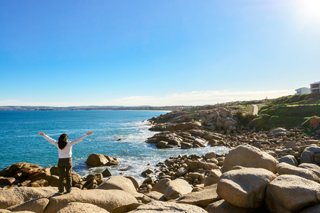 Woman standing at the edge of the rock and looking into the sea at Port Elliot, South Australia Stock Photo