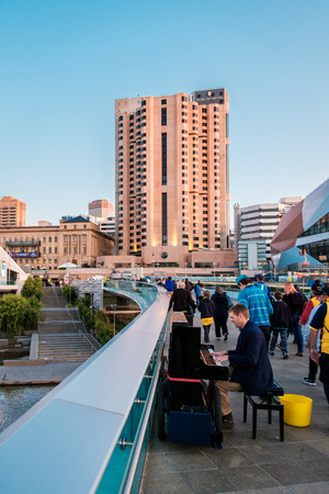 foot bridge: Adelaide, Australia - September 11, 2016: Man playing piano and people walking through Torrens foot bridge from Adelaide Oval after game in Adelaide city centre at sunset