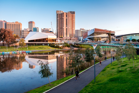 foot bridge: Adelaide, Australia - September 11, 2016: Torrens river bank with people walking through foot bridge in Adelaide city centre at sunset