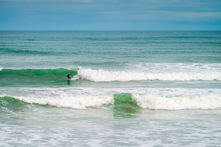 adelaide: Adelaide, Australia - August 14, 2016: Surfer sliding the wave at Middleton Beach on a day. Middleton beach is one of the most famous places for surfing in South Australia