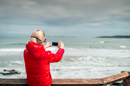 Woman taking pictures of surfers with mobile phone, Middleton, South Australia Stock Photo
