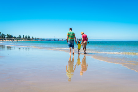 adelaide: Grandparents with grandson walking on the beach and holding hands