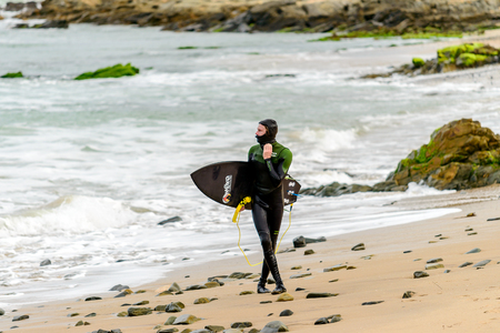 Middleton, Australia - August 14, 2016: Surfer holding his surfing board at Middleton Beach on a day. Middleton is one of the most famous places for surfing in South Australia