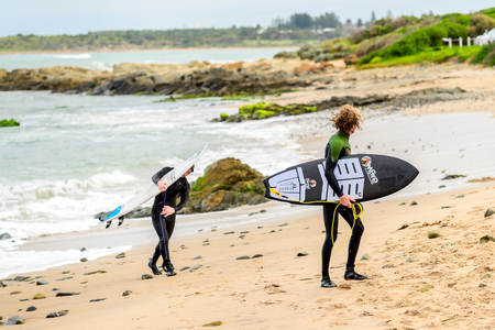 Middleton, Australia - August 14, 2016: Surfers with surfing boards getting out of water at Middleton Beach on a day. Middleton is one of the most famous places for surfing in South Australia