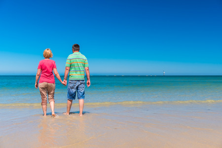 adelaide: Senior couple holding hands of each other at the beach Stock Photo