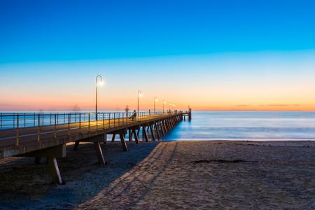 adelaide: People walking on Glenelg Jetty at sunet, South Australia