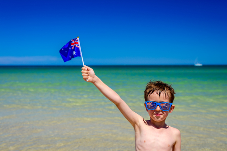 Cute smiling boy with  Australian flag standing on the beach on Australia day