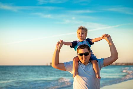 adelaide: Father giving son piggyback ride on beach